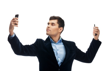 narcissism: Attractive man shooting himself with two smart phones on isolated white