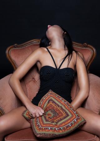 Seductive woman on a throne of pleasure