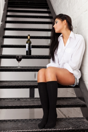 Tired of drinking girl sitting on stairs to nowhere photo