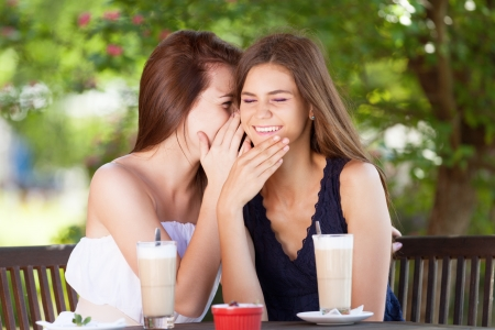 Two girls gossiping in cafe photo