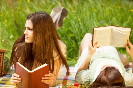 woman reading book: Two girls are resting in park with books