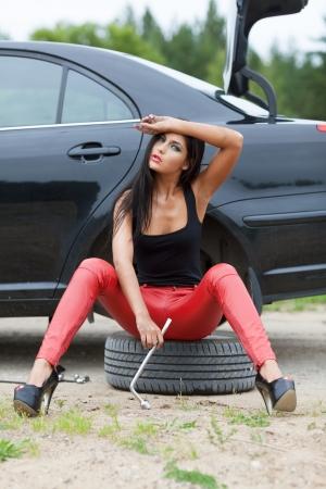 broken car: La muchacha atractiva est� cansado tratando de cambiar la rueda de coche roto Foto de archivo