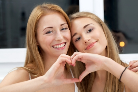 Two best friends showing their common heart Stock Photo