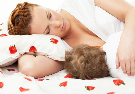 Mother breast feeding her child on the bed photo