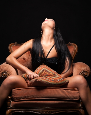 Horny girl pleasing herself sitting on the armchair Stock Photo