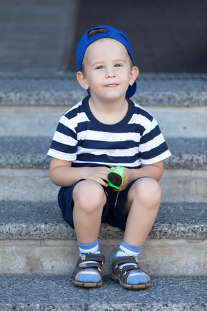 Lovely kid sitting on the stairs and waiting for a walk photo