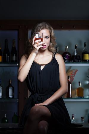botella de whisky: Mujer atractiva con el vaso de whisky que se sienta en la barra del bar
