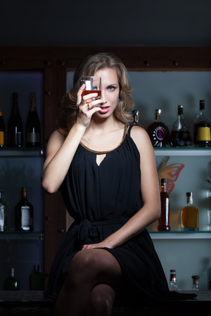 whiskey bottle: Sexy woman with the glass of whiskey sitting on the bar counter