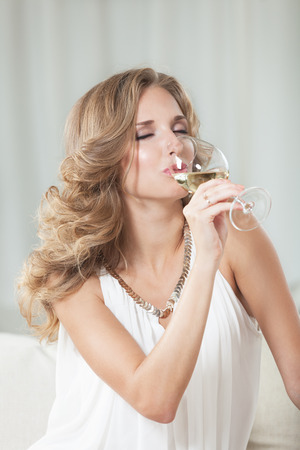Attractive girl enjoying white wine in the restaurant photo
