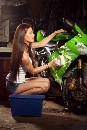 Woman washing motorcycle in garage and preparing it for a ride Stock Photo