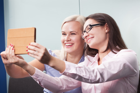 Two attractive women having video conference using tablet photo