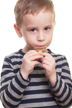 reluctant: Shy boy with candy on isolated white Stock Photo