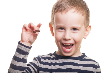 Happy boy with pill on isolated white Stock Photo