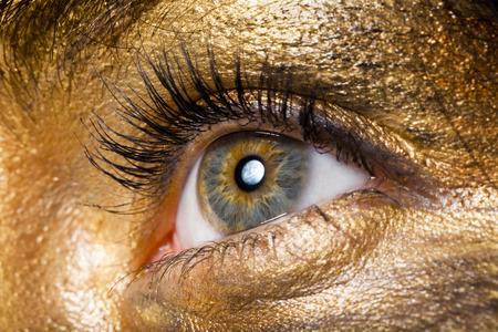Creative make-up technique: golden paint, macro shot photo