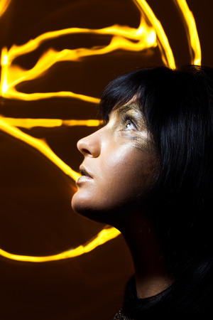 Creative make-up technique: golden paint and freeze light photo