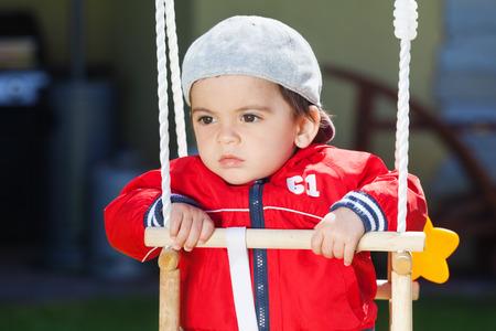 arabic boy: Pensive arabic boy swinging outdoors