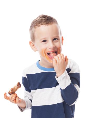 Cabrito adorable comer costillas a la barbacoa en el blanco aislado Foto de archivo