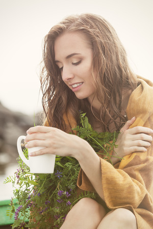 Wet and freezing woman in plaid enjoying a cup of tea with herbs after the rain Stock Photo