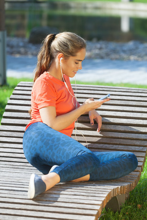 Young sporty girl having rest and enjoying good music Stock Photo