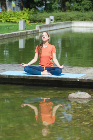 Young sporty attractive woman meditating next to the water Stock Photo