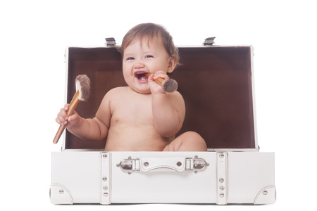 Cheerful little girl with two make-up brushes sitting in a suitcase on isolated white Stock Photo