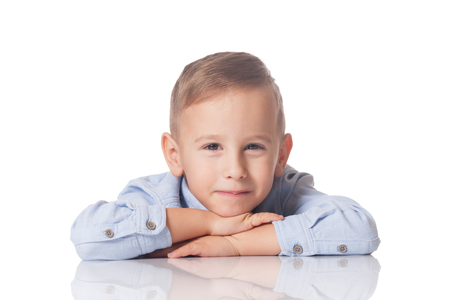 Studio portrait of a positive and smiling boy on isolated white