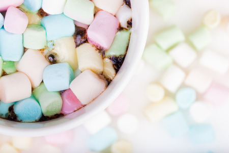 Lots of colorful marshmallow in the cup of coffee
