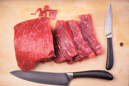 Sliced meat on the board with knives Stock Photo