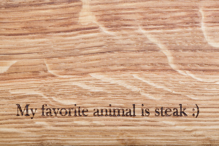Wooden desk with a text: my favorite animal is steak Stock Photo