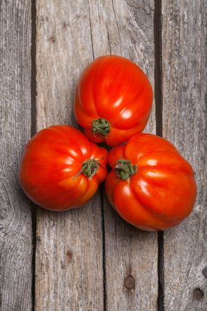 Tomatoes on the wooden vintage table Stock Photo