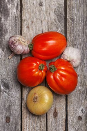 Tomatoes, onion and garlic on the vintage wooden table Stock Photo
