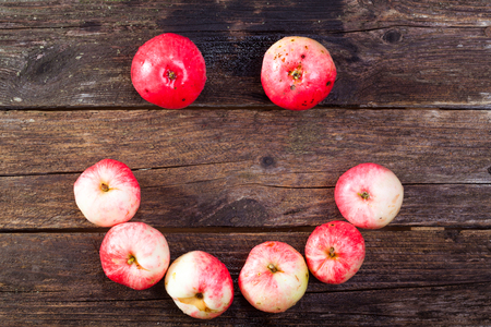 Smile made of red ripe apples on the vintage wooden table