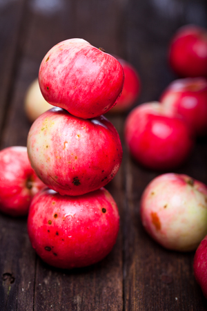 Tower made of red ripe apples on the vintage wooden table
