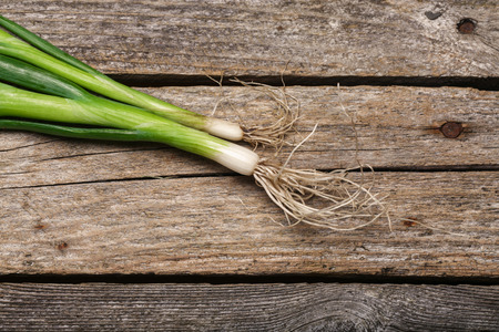 Green fresh spring onion on the vintage wooden table Stock Photo