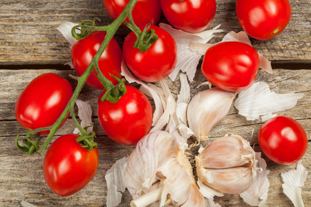 Fresh tomatoes and gloves of garlic on the wood