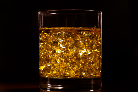 Golden hard liquor with ice on the wooden table Stock Photo - 88623533