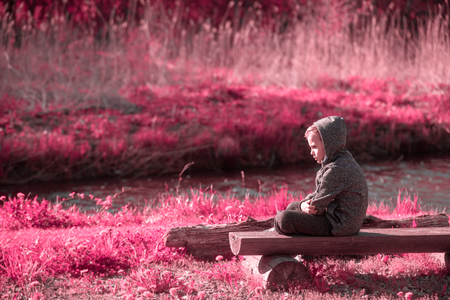 Vulnerable boy sitting at the river side Stock Photo - 104842032