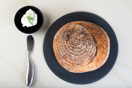 Wholewheat bread on black round plate with a serving of creamcheese