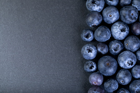 Fresh and ripe blueberries on dark stone plate