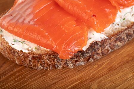 Sandwich with salmon on wooden board Stock Photo - 131873848