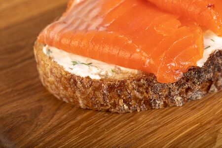 Sandwich with salmon on wooden board Stock Photo - 131872509