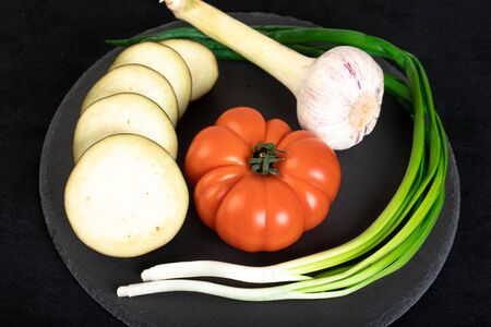 Assorted vegetables ob black wooden plate Stock Photo