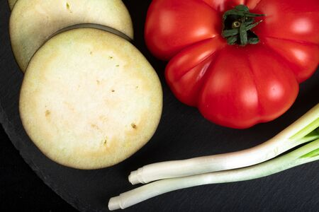 Assorted vegetables ob black wooden plate Stock Photo - 132740286