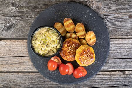 Lunch of fish cutlet with baby potatoes and leek sauce served on a black stone plate Stock Photo - 146563332