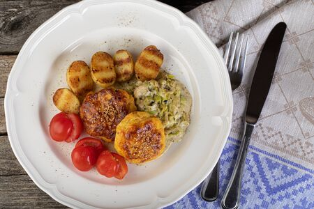 Lunch of fish cutlet with baby potatoes and leek sauce in a rustic setting Stock Photo