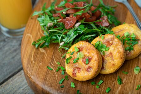 Egg muffins with bacon and cherry tomatoes served with fresh rocket salad on a wooden board Stock Photo