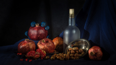 still life with bottle, pomegranate and walnuts on hellouvin Stock Photo