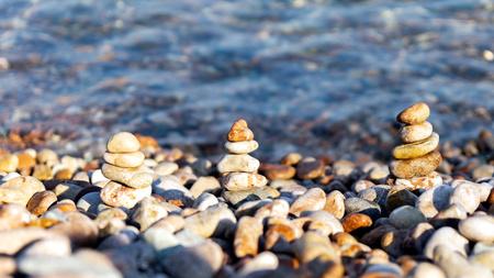 Steinpyramide auf der bunten Kiesdecke am Strand mit kristallklarem Wasser