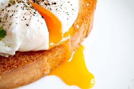 Los huevos escalfados sobre una tostada Foto de archivo - 68306915