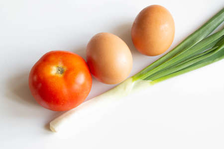 Eggs, green onion and tomato on white background. Ingredients for breackfast 版權商用圖片